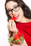 Beautiful woman with eyeglasses eating strawberries Royalty Free Stock Photography