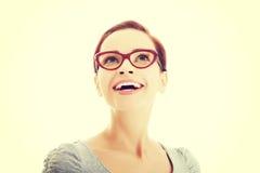 Beautiful woman in eyeglasses looking up. Stock Image