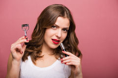 Beautiful woman with a eyelash curler. Beautiful smiling woman holding an eyelash curler Stock Photo