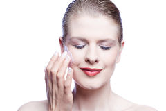 Beautiful woman with eyes closed applying face cream Stock Photo