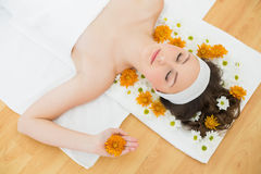 Beautiful woman with eyes closed and flowers in beauty salon Royalty Free Stock Image