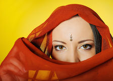 Beautiful woman eyes in indian traditional bindi. Young beautiful woman eyes in indian traditional jewellary, bindi , sari dress and makeup. yellow background Stock Image