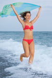 Beautiful woman with fabric running on beach Stock Photography