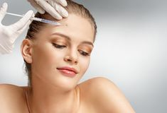 Beautiful woman face and beautician hands with syringe. Makes cosmetic injection in forehead. Clean Beauty concept Stock Images