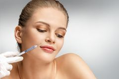 Beautiful woman face and beautician hands with syringe making rejuvenate injection. Clean Beauty concept Royalty Free Stock Images