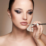 Beautiful woman face. beauty girl with make-up.applies lipstick Royalty Free Stock Image