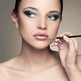 Beautiful woman face. beauty girl with make-up.applies lipstick Stock Images