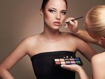 Beautiful woman face. beauty girl with make-up.Makeup artist applies lipstick Royalty Free Stock Photos