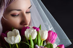 Beautiful woman face with a bouquet of tulips Royalty Free Stock Image