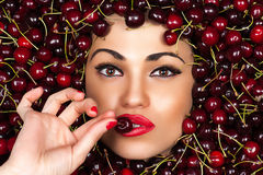 Beautiful woman face with cherry in hand Stock Photo