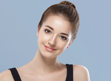 Beautiful woman face close up portrait young studio on blue Stock Images