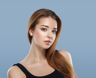Beautiful woman face close up portrait young studio on blue Royalty Free Stock Images