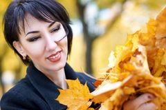 Beautiful woman face closeup with handful of yellow leaves in autumn outdoor, trees on background, fall season Stock Photos