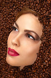 Beautiful woman face in coffee beans Royalty Free Stock Photos