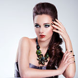 Beautiful woman face with fashion green make-up and jewelry on h Royalty Free Stock Photography