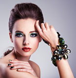 Beautiful woman face with fashion green make-up and jewelry on h Stock Photography