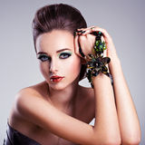 Beautiful woman face with fashion green make-up and jewelry on h Royalty Free Stock Photos