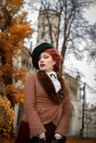 Beautiful woman face in the hat and red hair autumn trees. Beautiful woman face in the hat and red hair with sad eyes - countess autumn trees royalty free stock photo
