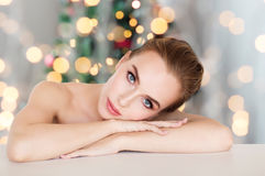 Beautiful woman face over christmas lights. Beauty, people, holidays and bodycare concept -beautiful young woman face and hands over christmas tree lights Stock Photos