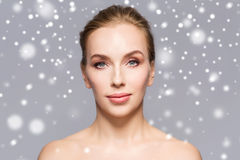 Beautiful woman face over gray background and snow Stock Photography
