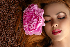 Beautiful woman face with peony on coffee beans Royalty Free Stock Images