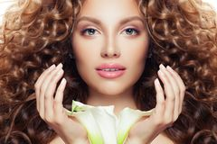 Beautiful woman face. Perfect model girl with long curly hair, clear skin and lily flower royalty free stock photography