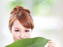 Beautiful woman face portrait with green leaf Stock Image