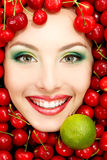 Beautiful woman face with red ripe big fresh cherry and lime Royalty Free Stock Image