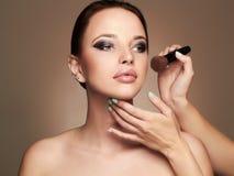 Beautiful woman face. Skincare foundation.Makeup artist applies skin tone Stock Photos