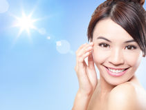Beautiful woman face with sunshine and sky. Beautiful woman face with sunshine and blue sky, concept for summer skin care and sun block, asian beauty Stock Image