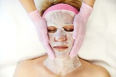 Moscow, Russia, 02.02.2019: Beautiful woman with facial mask at beauty salon. Applying facial mask at woman face at. Beautiful woman with facial mask at beauty stock photo