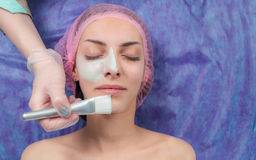 Beautiful woman with facial mask at beauty salon. Cosmetician Applying Facial Beauty Mask For Young Woman At Spa beauty Salon. Closeup cosmetologist applying Stock Photography