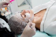 Beautiful woman with facial mask at beauty salon. Royalty Free Stock Image