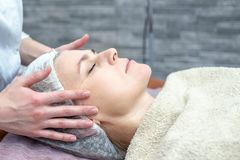 Beautiful woman with a facial mask at a beauty salon stock photography