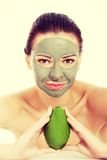 Beautiful woman with facial mask holding avocado Stock Photos