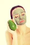 Beautiful woman with facial mask holding avocado. Royalty Free Stock Photos