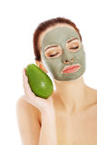 Beautiful woman with facial mask holding avocado. Stock Photography