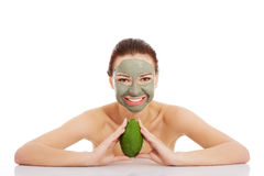 Beautiful woman with facial mask holding avocado. Stock Photo