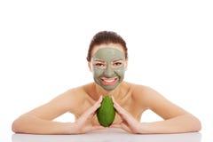 Beautiful woman with facial mask holding avocado. Stock Photo