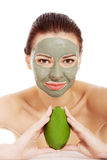 Beautiful woman with facial mask holding avocado. Royalty Free Stock Image