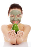 Beautiful woman with facial mask holding avocado. Stock Image