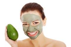 Beautiful woman with facial mask holding avocado. Stock Photos