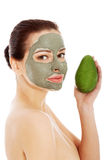 Beautiful woman with facial mask holding avocado. Stock Image