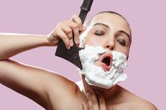 Woman has shave. Beautiful woman with fake mustache, beard and axe on pink background has shave royalty free stock photos