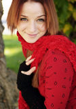 Beautiful Woman in Fall Season. A beautiful woman with a red hair, red scarf, and red top Royalty Free Stock Photo