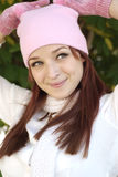 Beautiful Woman in Fall Season. A beautiful woman with a red hair, white scarf, and pink bonnet and gloves Stock Image