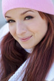 Beautiful Woman in Fall Season. A beautiful woman with a red hair, white scarf, and pink bonnet and gloves Royalty Free Stock Photo