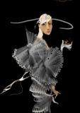 Beautiful woman in a fancy dress on black, holding one eye shut Royalty Free Stock Image