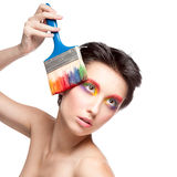 Beautiful woman with fantasy makeup holding brush Royalty Free Stock Image