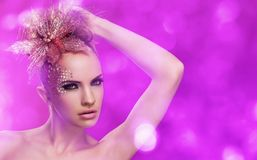 Beautiful woman with fantasy makeup. On a violet background Royalty Free Stock Photo